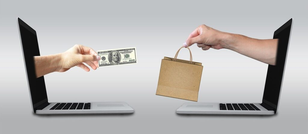 Two hands reaching to each other from two computers. The one is holding money and the other is holding a bag with some products